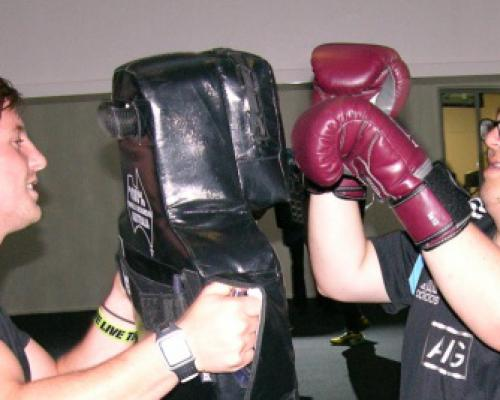 An image of Sam boxing with his Personal Trainer at the gym.